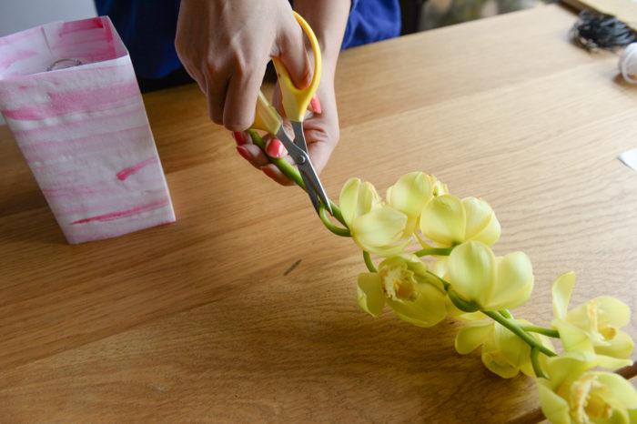 4.半紙の中にガラス瓶を入れ、シンビジウムの枝を吸水しやすくするため、斜めにカットし瓶に生ける。