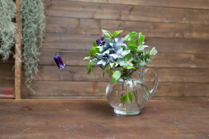 4. 最後にアジサイを生け、全体が動かないよう固定する。ピッチャーの注ぎ口に花材を全て傾け、フチを見せて清涼感を出す。
