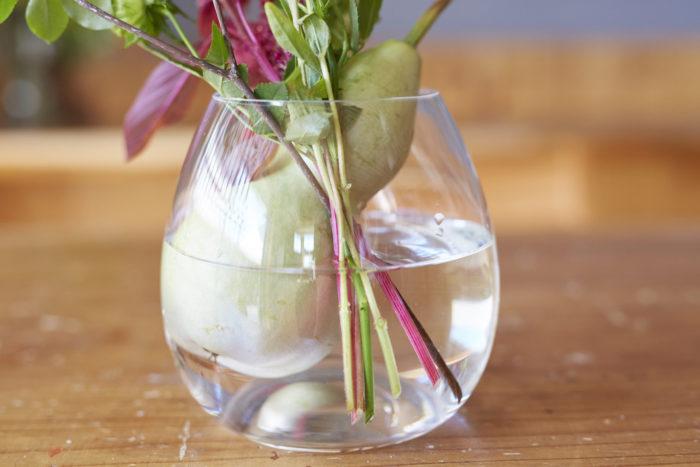 3.残りの花材は全て重ねて切る。2と同様、ヒョウタンの後方に生ける。花瓶の中の茎部分にも意識を向け、流れを整える。