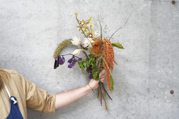 2. 花の自然な向きを意識して組み合わせる。ケイトウ、パニカム、アワ、ドリコスルビーの垂れ下がる花材はそれぞれ向きを変え、動きを出す。
