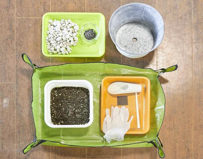 今回準備したものはこちら。左上より鉢底石、緩効性肥料、器、土入れ、割りばし、鉢底ネット、ビニール手袋、崩した土やごみを入れるトレー、草花用培養土、作業用シートです。