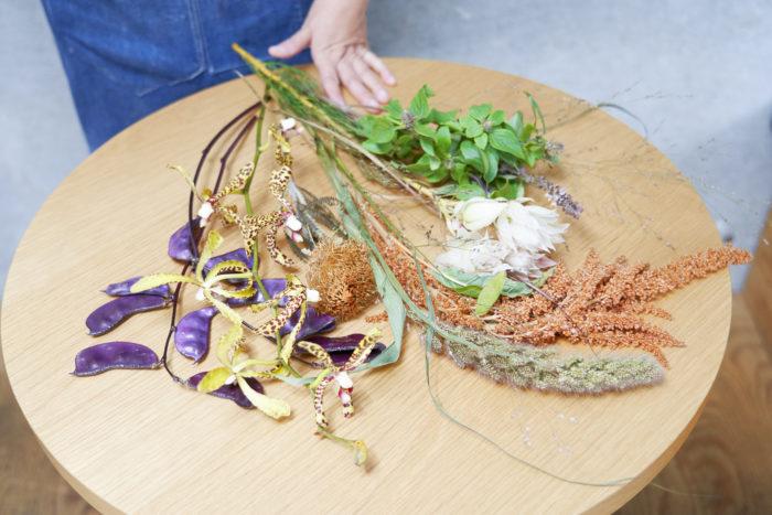 1.机に花材を並べ、花瓶に生けた時に水にあたる茎下部の葉を手でとる。まずは花全体を見て、生ける花瓶を意識しながらあしらいをつくろう。