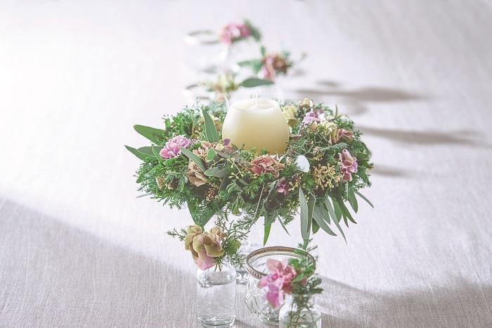 リースの飾り方は壁に掛けるだけではありません。テーブルに置いて、テーブルコーディネートの主役にしてみましょう。脚の付いたコンポート皿や平皿に置いて、周囲に余った花材を小瓶に入れて、散らすように飾ったら、素敵なテーブルコーディネートになります。 ゲストを招いてのお食事や、記念日のお家ディナーに活用できるアレンジです。