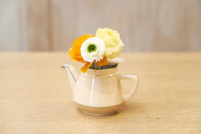 2.隙間を空けて蓋を閉める。メイン花材のラナンキュラスはオレンジ・黄色・白の順番に生ける。濃い色のオレンジを奥に生けることで奥行きが出る。