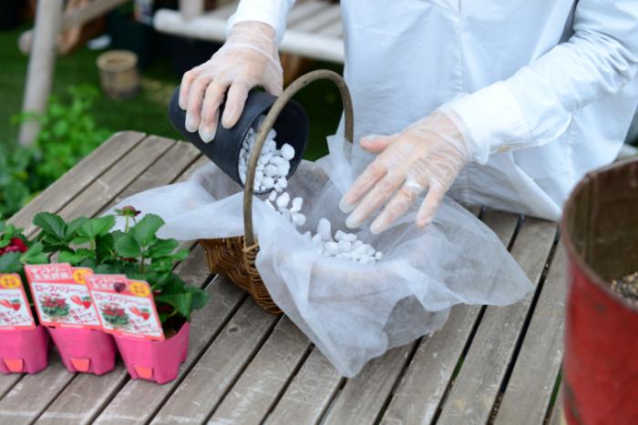 土が漏れないようにバスケットに不織布を敷き、鉢底石、野菜用の培養土の順に入れます。