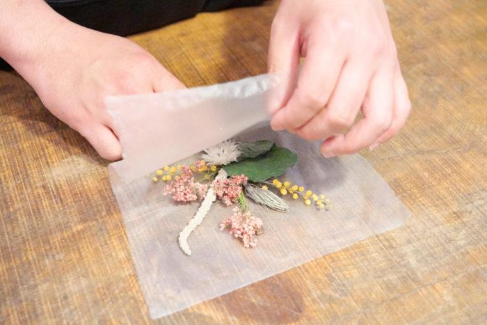 2. 花が動かないように、大きいものを支点に押さえながら紙を半分に折る。後から切るので端がきれいにそろっていなくても大丈夫です。