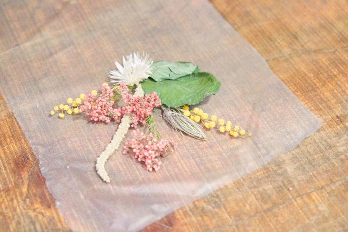 プレスンシールを30㎝ほど切り、上半分に花を置きます。ポイントになる花を1つ選び、その花が目立つように配置するとメリハリが出ますよ。