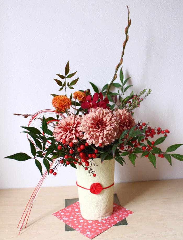 和紙と祝儀袋についている水引を巻き付けるだけで、いつもの花器がグッと和の雰囲気に。花器の下にも折り紙を敷くと、よりおもてなし感がでますよ。