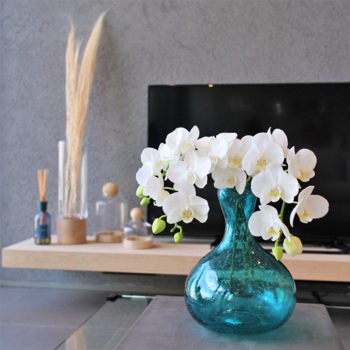 青い花瓶と白い花びらがリビングを華やかに