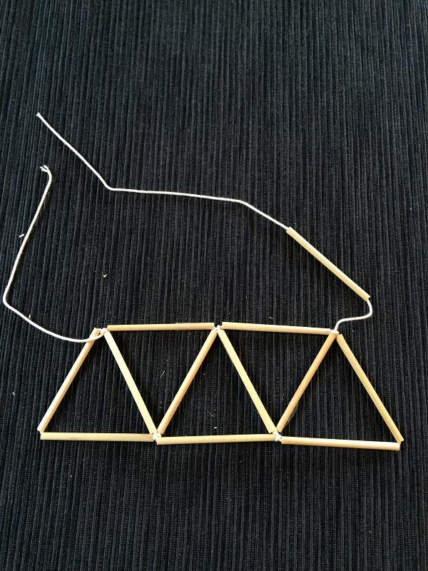 ④11本使って5つの三角形ができて結んだ後、最後の1本を糸に通します。