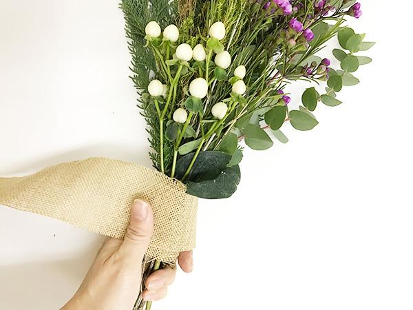 ③まとめます  植物を束ねたら、麻紐でしっかりとぎゅっとまとめます。まとめた上から好みのリボンなどで飾ります。今回は麻のテープを巻いてラフィアテープで結んで飾りました。