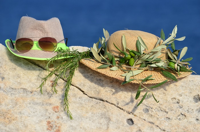 Summer vacation concept, two hats, sunglasses, olive wreath and sprig of rosemary on marble rock against blue bokeh background