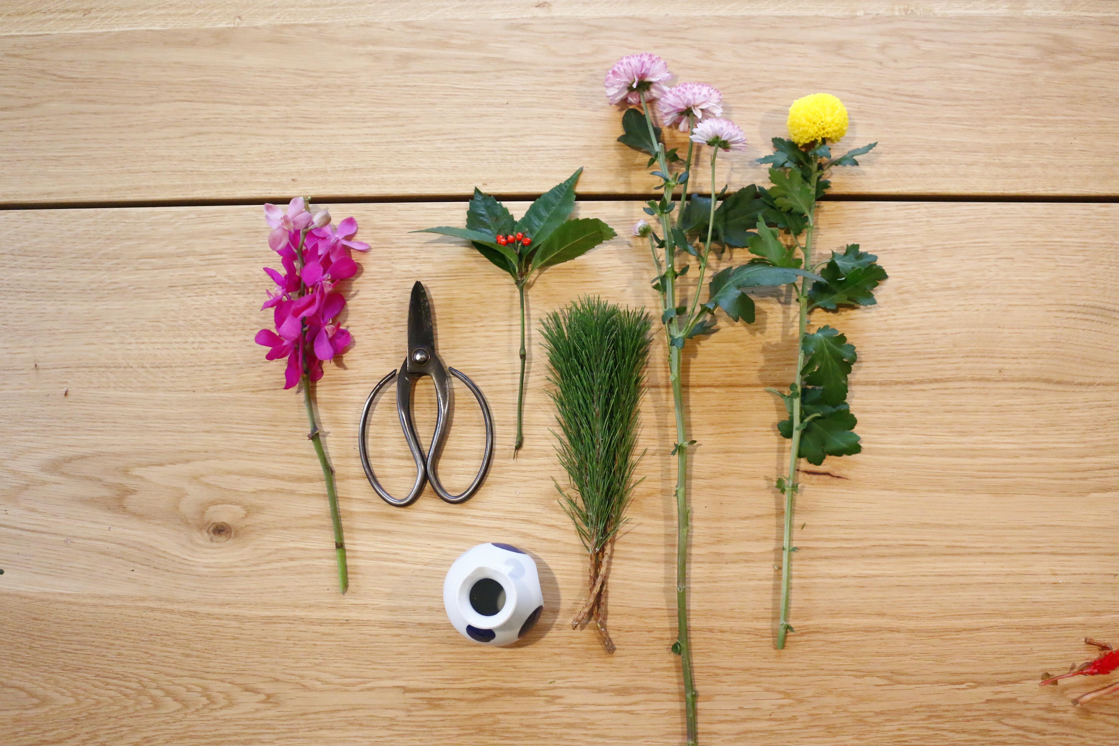 手順は簡単です。100均でも手に入るような小さな徳利に活けていきます。  花材は、菊・松・千両・蘭にしました。長さはある程度切って、余分な葉っぱは落とします。