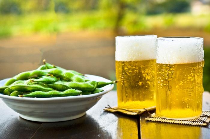 豆自体を食べるという習慣としては、枝豆の方が断然多いかもしれません。  枝豆として未成熟大豆を食するようになったのは17世紀末からです。そして、未成熟大豆を食したのは世界で日本人が初めてといわれています。  枝豆は江戸時代に庶民の味として普及しました。背中に枝豆を背負った枝豆売りが売り歩き、買った人も道を歩きながら枝豆を食べる、現代でいうところのファーストフードのフライドポテトのような存在だったようです。枝豆は枝から外すと一気に鮮度が落ちるためその売り方は理にかなっていると言えます。  現代では「とりあえず」と言えば、枝豆とビールですね♪
