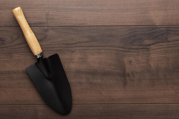 black gardening shovel on the wooden table