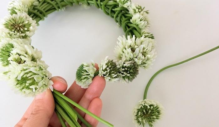 お好みの長さまで編んだら最初の花を最後のまとめた茎部分の上に乗せ、