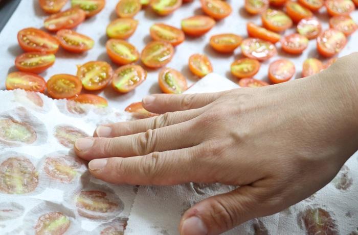 ミニトマトの切り口から出る水気を、キッチンペーパーなどで軽く吸い取ります。