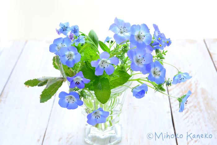 ▼ガラスのグラスにミントや同じ時期に咲く草花、忘れな草やシノグロッサムで水色のアレンジメント。