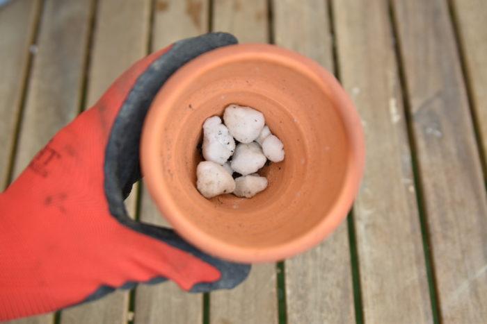鉢底ネットを被せたら鉢底石を入れます。  鉢底石は通気性と排水性を高める役割があるので、必ず入れてください。