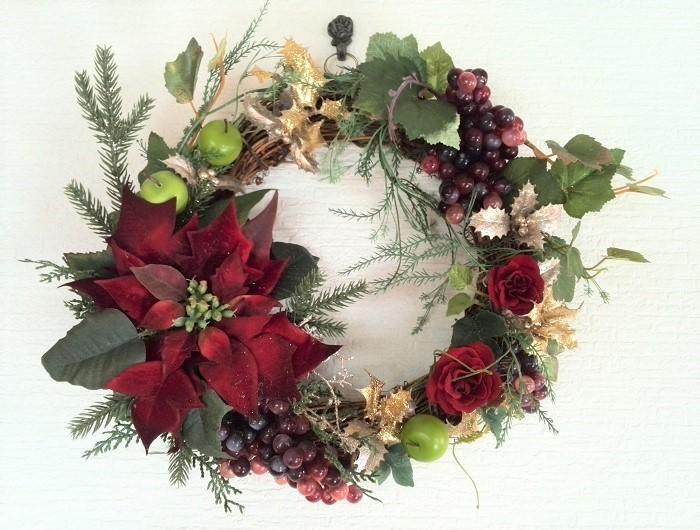 リース台に、アーティフィシャルフラワーのポインセチアをメインに飾り付けました。ブドウやリンゴ、キラキラしたヒイラギなどもポイントに使っています。