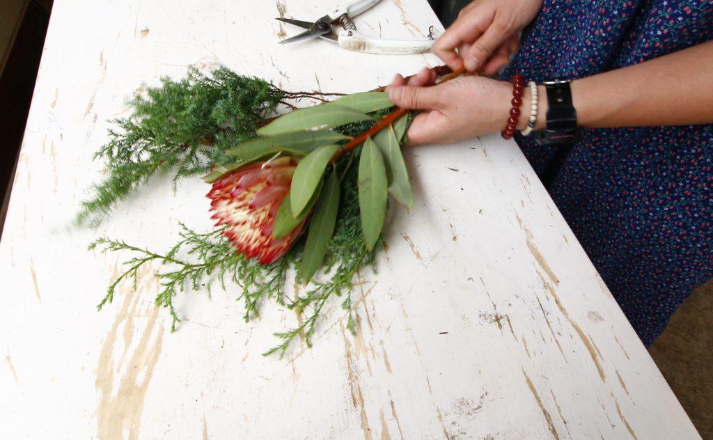 3.花材を組もう  それでは花材を組んでいきます。背中にヒムロスギを置いて真ん中にメインとなるプロテア。花を組むときに置いてやると、組みやすいです。