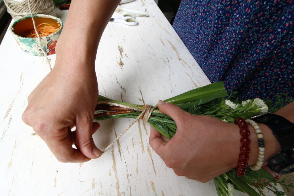 ぐるぐると茎を巻いていき、輪ゴムが隠れたら一番最初のわっかに麻ひもを通して、この状態に。