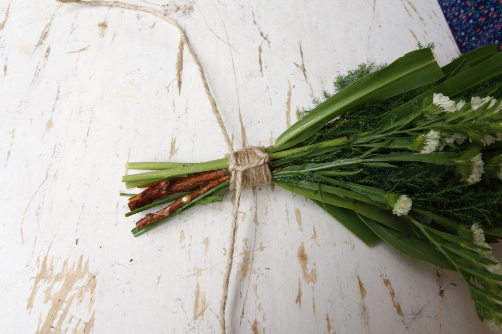 茎下部分側のひもと、先ほどわっかに通したひもを、かた結びします。