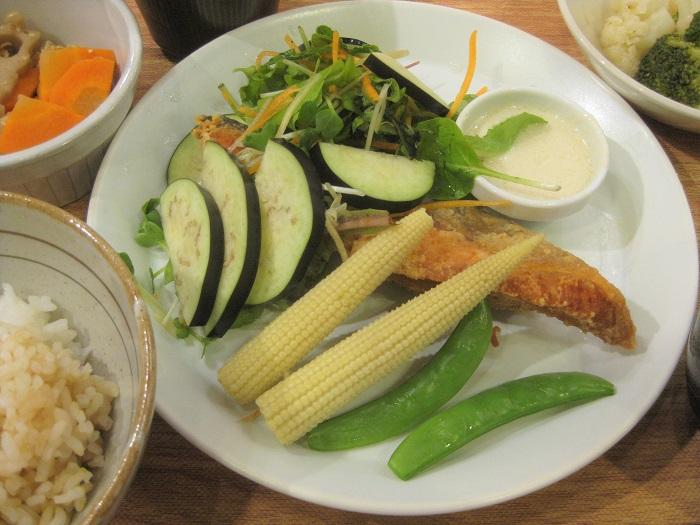 丸の内タニタ食堂では、2017年7月24日~29日の期間限定でナス「ごちそう」を使った週替わり定食が提供されました。※現在は提供されていません。  メニュー名は、「鮭の唐揚げとナス『ごちそう』のサラダ仕立て~バーニャカウダソース~」です。  こちらは、サカタのタネと、タニタが共同で開発したヘルシーメニューで、ナス「ごちそう」の魅力を全面に引き出したレシピになっています。  当日、このメニューを試食させていただきました。  ナス「ごちそう」の爽やかさと甘みを生かすソースと新鮮野菜、かりっと揚げた鮭とお豆の入った副菜など、組み合わせのバランスが良く、毎日こんな定食が食べられたら健康で幸せだと思いました。