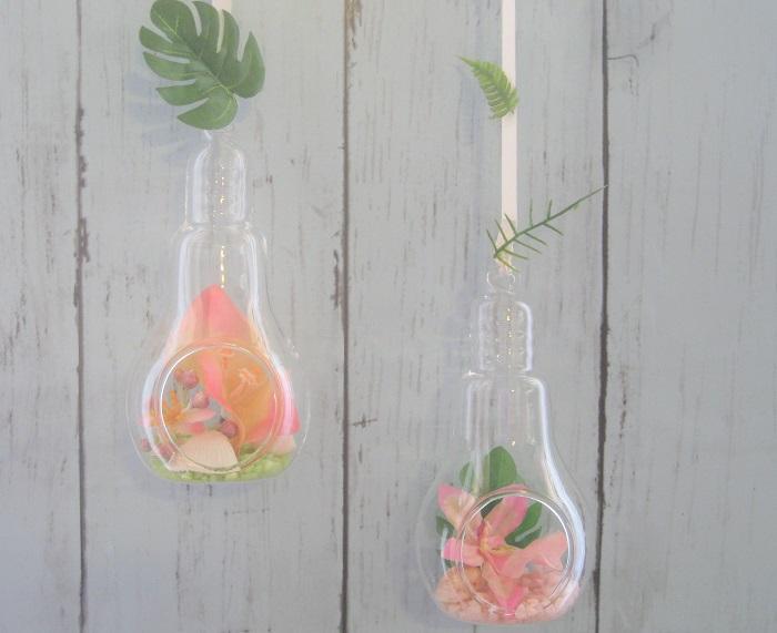 カラーサンドを薄く敷いた後に、貝殻と、アーティフィシャルの南国風の花とモンステラの葉を飾りました。