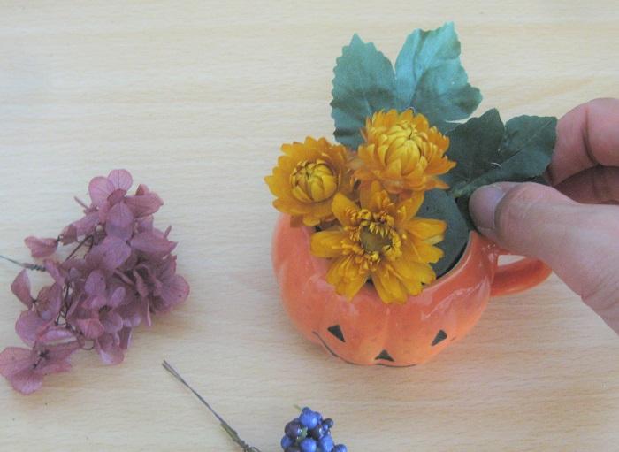 ワイヤーが長いものはカットして、オアシスに挿していきます。今回は、同じ花材はまとめてアレンジする方法(グルーピング)でデザインします。