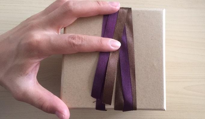 3周目のところで端を切り、両面テープでリボンを固定します。写真だと人差し指でおさえているあたりです。
