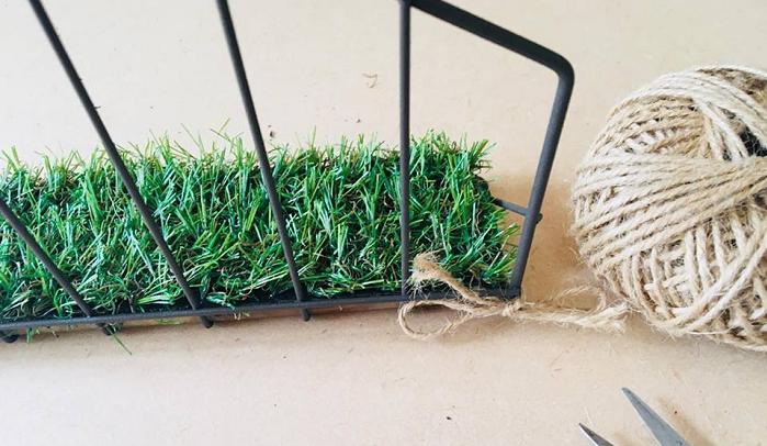 この人工芝のはじに穴を開け、取り外しができるようにします。  この人工芝は、見た目よりもかなり固いので、ハトメ抜きで固い部分を抜いた後、ハンダゴテで溶かしながら開けます。  麻ひもを通して、棚に結び付け固定します。