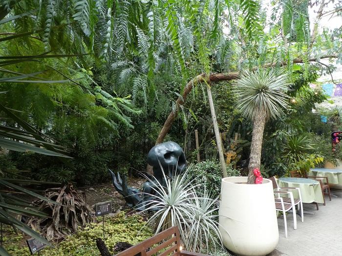 中へ進むと、不思議なフォルムのモニュメント? とよくマッチした植栽。このあたりはまるでジャングルのようです。画面左に見えるのは、2016年夏に開花し、枯れてしまったアガベ サルミアナ var. フェロックス。