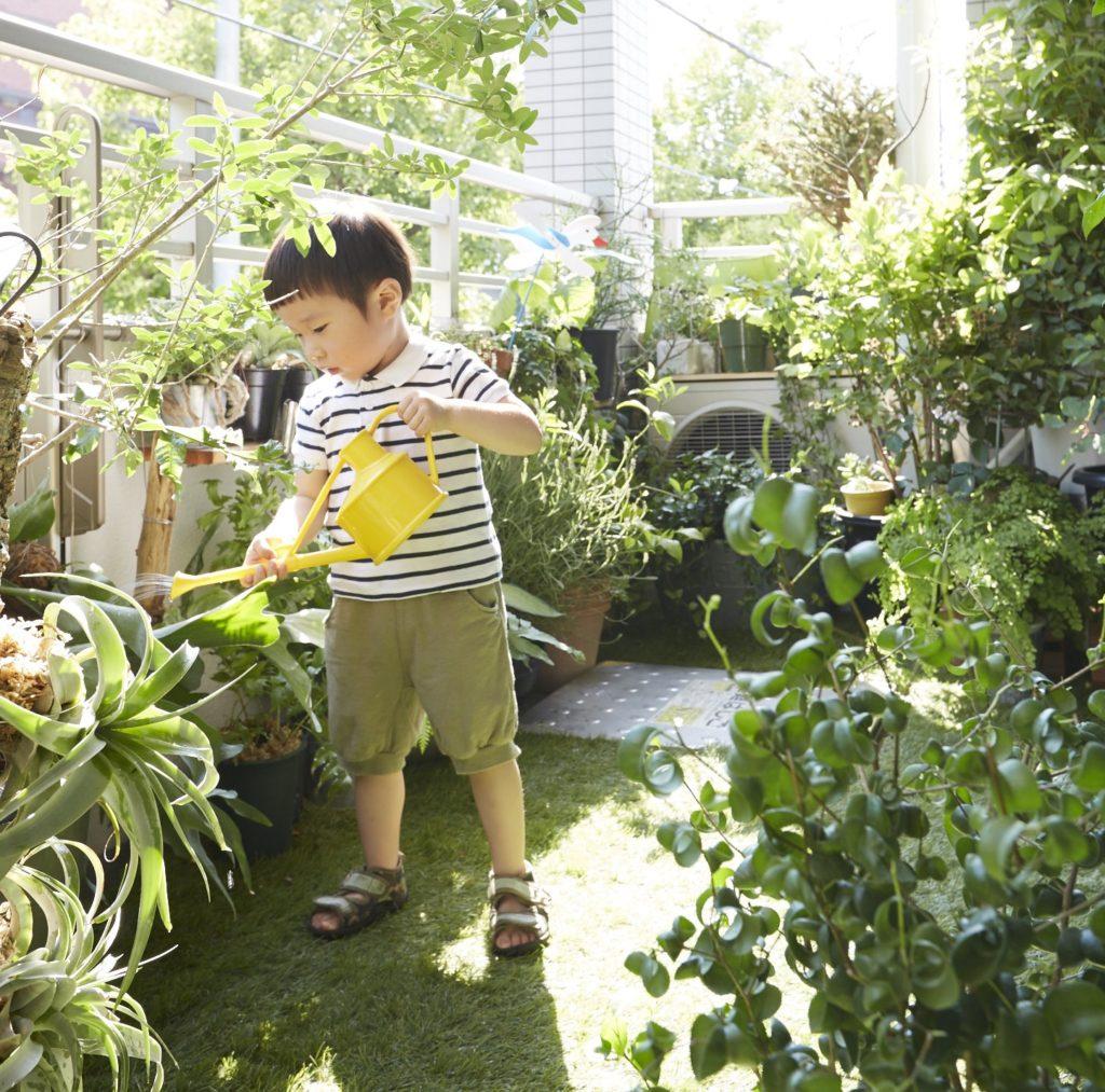 足元には緑色の絨毯のように芝が広がる。人工芝を使うことで無機質なイメージのベランダがまるで庭のような空間に早変わり。「人工芝を敷いた理由は子どもと一緒に遊びたいという思いから敷いてみました」というKさん宅のベランダ。