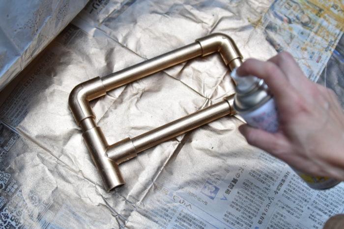 新聞紙やダンボールの上で塗装します。今回は真鍮色の金メッキスプレーを使用しました。  筆などで塗るタイプよりも、スプレータイプの方が楽なので初心者の方にオススメです。  ポイントは少し離れた場所から全体的にムラが出ないように吹きかけることです  塗装した後はしっかりと乾燥させましょう。生乾きのまま裏返してしまうと色落ちの原因になってしまいます。