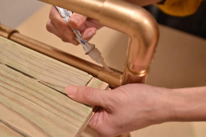 ⑬ 完成した骨組みに棚板を乗せて、長さを調節します。  棚板が長すぎる場合は、棚板をノコギリで切ってください。逆に棚板が短い場合は、塩ビパイプをノコギリで短くしてください。  調節が終わったら、四隅を瞬間接着剤で接着します。