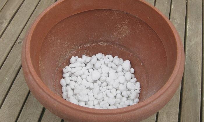 コンテナの底に鉢底ネットを敷き、鉢底石を入れます。(器の1/5程度)