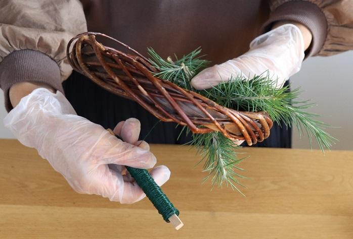 常緑樹を3本ほど束ねて根元から2~3cmの部分を持ってリースに沿わせ、リースワイヤーを内側から外側へ常緑樹の根元に2~3周巻き、留めます。ワイヤーをしっかりと引っ張って固定させます。  *写真はリースの巻き付け方のイメージです。完成写真のリースと違う常緑樹を使っています。