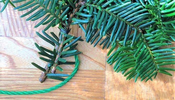 束にしたもみの木を芯にするロープに針金で巻き付けていきます。