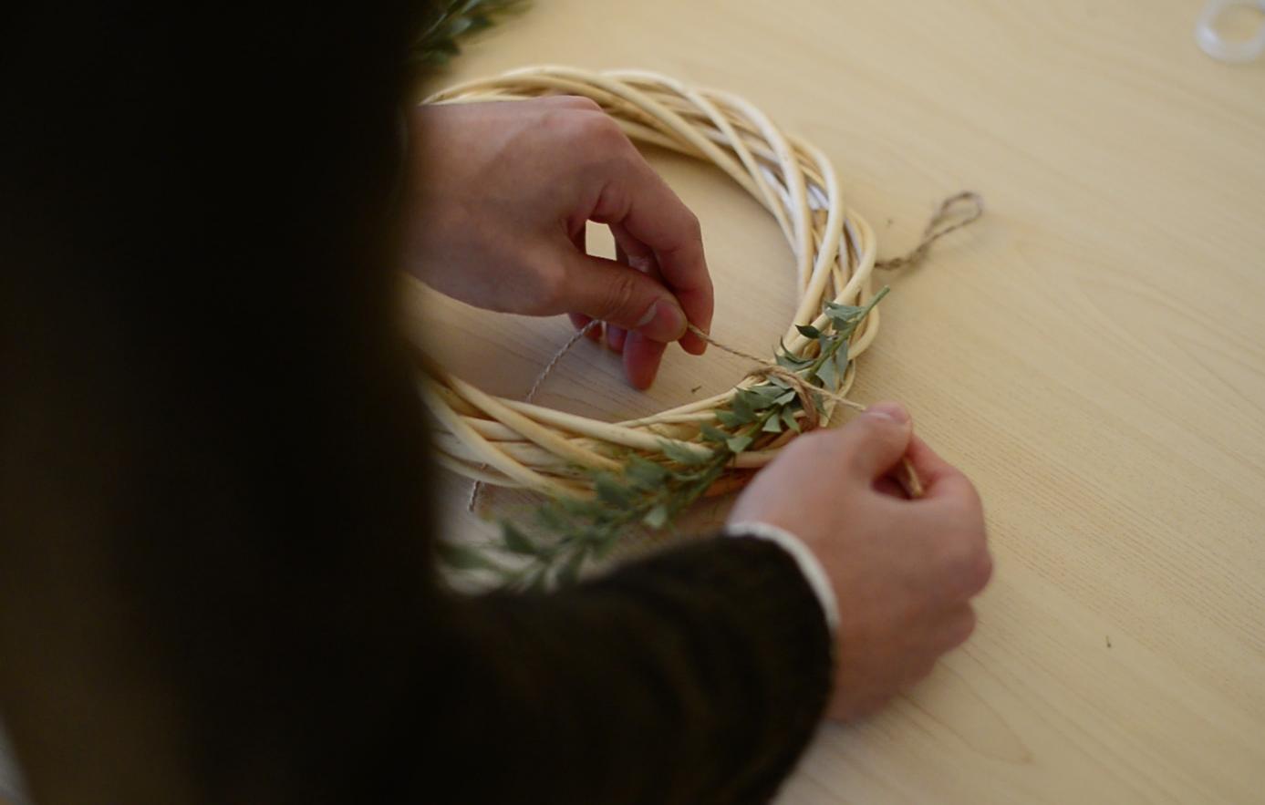 リースを作るときは同じ向きの流れに沿って作っていくときれいな形に。今回は葉の先端が時計回りに見えるようにリース台につけていきます。。  まずは茎の下部分を麻ひもで止めます。麻ひもの部分が隠れるように、次の葉を上に乗せていきます。