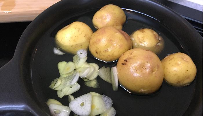 2. アヒージョ用の鍋にジャガイモとニンニクを入れ、鍋の半分くらいの量のオリーブオイルを注ぎます。