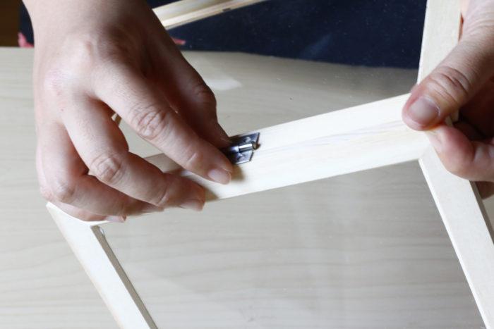まず、フォトフレームの中の透明フィルムだけをボンドで淵に接着し、蝶番を付ける場所の目星を付けます。