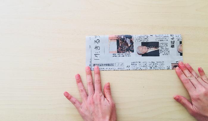 1. 1/8の新聞紙をさらに半分に折ります。