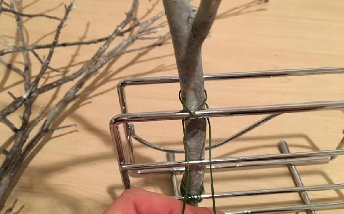 2 塗料が完全に乾いたら、ワイヤーでまな板立てに木を固定させていきます。