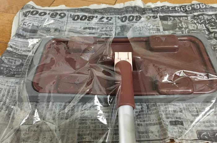 掃除が終って新聞紙を外すときに、取り外しが楽なようにシートを装着する部分にラップを当てます。