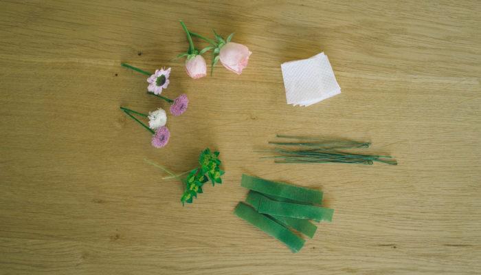 お花を茎の部分を2-3cm残して斜めにカットします。ワイヤーを巻くので、若干茎を長めに残した方が作業しやすいです。余分な葉っぱがある場合には取ります。保水するために茎に巻いて利用します。利用するお花の数だけ、巻きやすいサイズにカットしておきます。フローラテープをカットします。ここでは、お花に巻き付けるのに6-7cm程度、ひもに巻き付ける時に使うものを15cm程度、ひもにお花を付けていくのに5cm程度にカットして使っています。長さはご自身で扱いやすいサイズに調整して、お好みでカットしてください。