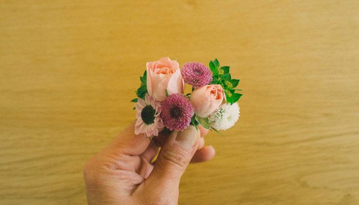 作りたいブレスレットのイメージを思い浮かべて、花を使いながら小さいブーケのようにまとめてみます。向かって右から上下に順番にひもに取り付けます。フローラテープをあらかじめのばしておいて、お花のワイヤー部分をひもに巻き付けていきます。ここでは、ブプレリウム→サンティニ・カリメロ(白)→サンティニ・カリメロ(紫)→スプレーバラ→スプレーバラ→サンティニ・カリメロ(紫)→ブプレリウム→サンティニ・インヤンの順番で巻き付けています。