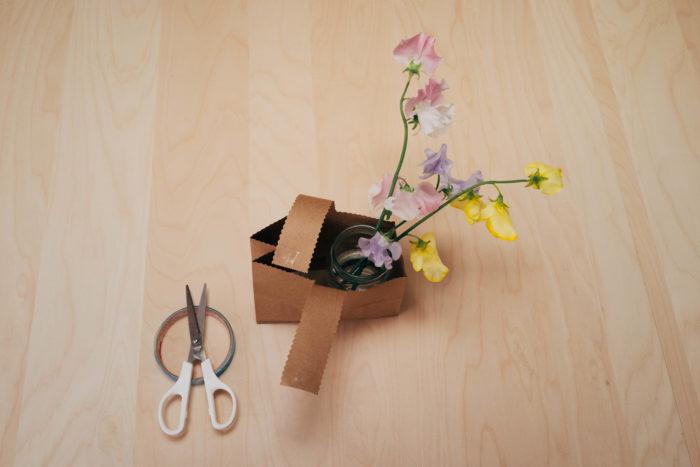 5. ストック、スイトピーを飾る空き瓶をクラフト袋の置き、高さに合わせて飾りたい花をカットします。6. 持ち手の部分を長さを調整しながら、両面テープで留めて出来上がりです。