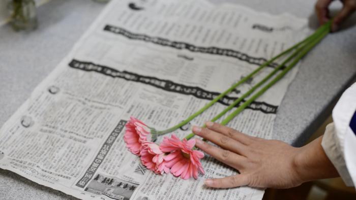 ガーベラの花が隠れる位まできつめに新聞紙で巻く花びらが曲がらないように丁寧に巻きます。