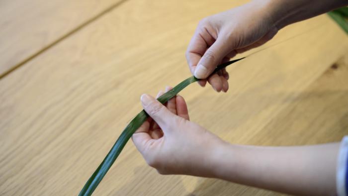 2.細くカットした、ハランの葉にの中央に縫う様にワイヤーを通します。これを全体の半分の数(5本~7本程)作ります。